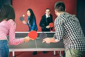 stock photo of ping pong  - Two couples of young people playing ping pong in a hostel  - JPG