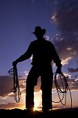 pic of wild west  - A cowboy silhouetted by a beautiful sunset holding a rope and a halter - JPG