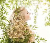 stock photo of natural blonde  - Hair in Green Leaves Natural Treatment Care Woman with Long Curly Blond Hairs Back view over White - JPG