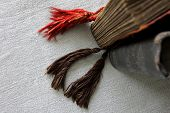 pic of tassels  - Top view of two old tattered vertical books or photography albums standing on a rough grey retro cloth - JPG