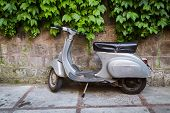 image of vespa  - Moped parked on the street near the fence, waiting for his master moped beautiful background pictures.
