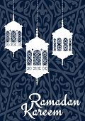 stock photo of kareem  - Ramadan Mubarak greeting card template with oriental lantern white silhouettes and wishes Ramadan Kareem on blue arabic seamless pattern - JPG
