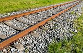 pic of train track  - Rusty train tracks on a bed of concrete sleepers and pebbles  - JPG