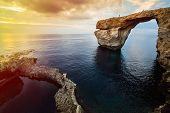 picture of gozo  - Azure Window natural arch famous landmark and popular tourist spot on Gozo island Malta Mediterranean at dramatic sunset - JPG