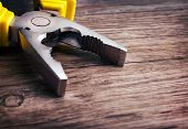 picture of pliers  - Close up of a multitool pliers on wooden background - JPG