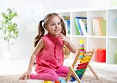 picture of nursery school child  - happy child girl playing with abacus toy in nursery - JPG