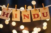 image of hindu  - The word HINDU printed on clothespin clipped cards in front of defocused glowing lights - JPG