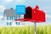 picture of postbox  - Red email postbox against house in the distance - JPG