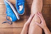 image of knee-cap  - Unrecognizable injured runner sitting on a wooden floor background - JPG