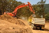 foto of track-hoe  - Exchavator track hoe loads a dump truck with top soil and loose dirt at a new commercial construction development project - JPG