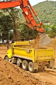 stock photo of track-hoe  - Exchavator track hoe loads a dump truck with top soil and loose dirt at a new commercial construction development project - JPG