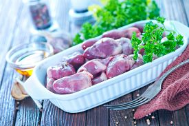 picture of giblets  - raw hearts on plate and on a table - JPG