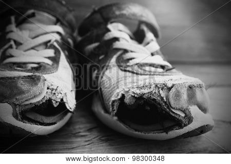 Old shoes with holes worn down shabby for homeless clothing