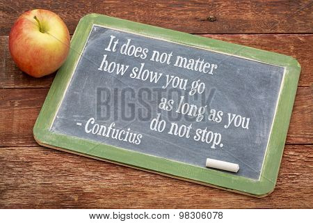 It does not matter how slow you go as long as you don not stop - Confucius quote on persistence- words on a slate blackboard against red barn wood