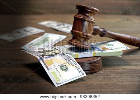 Bundle Of Money, Judges Gavel And Soundboard On Wooden Table