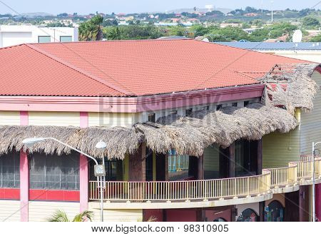 Tropical Building With Red Tile Roof And Thatched Awnings