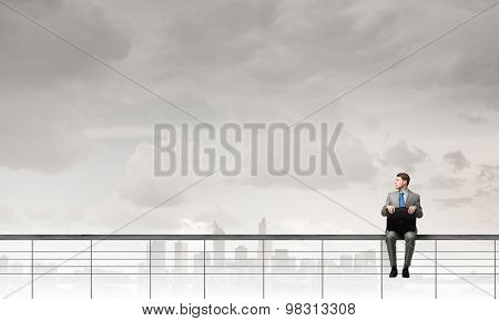 Young businessman sitting on parapet with briefcase in hands