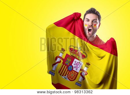 Fan holding the flag of Spain on yellow background