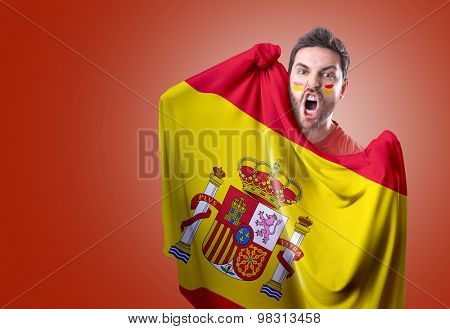 Fan holding the flag of Spain on red background
