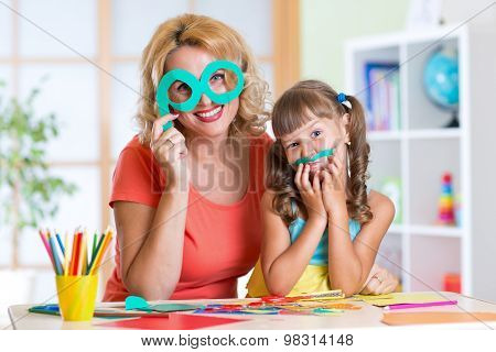 Child with woman have a fun cutting out scissors paper in preschool