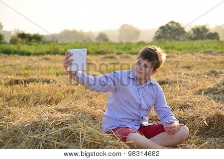 Boy Teenager Playing On A Tablet In The Field