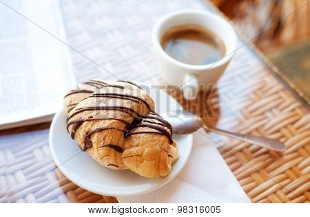 Cup of coffee and a croissant on the table