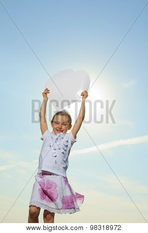 young child holding heart over the sky