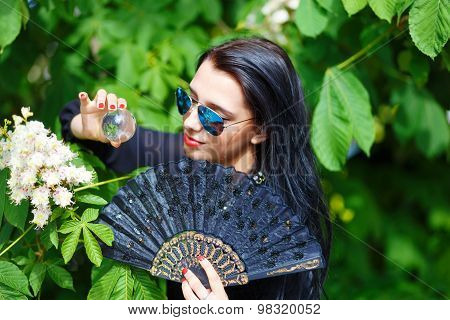 Beautiful woman with flowers, glamour white fur and sun glass, posing next to blooming magical sprin