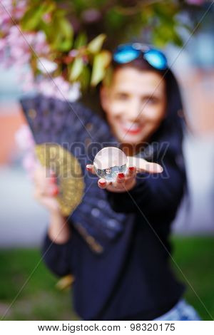 Young woman smelling a beautiful sakura blossom, purple flowers. Spring Magic, Magical Glass sphere