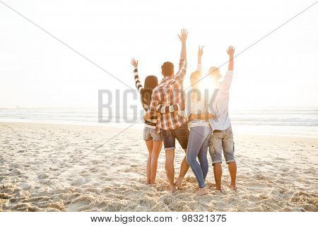 Group of friends at the beach and watching the sunset