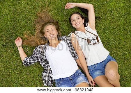 Female best Friends lying on the grass and having a good time together