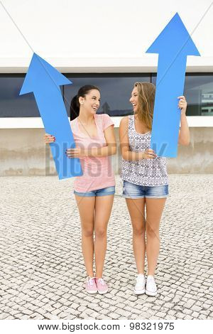 Two beautiful and happy girls holding a giant blue arrow