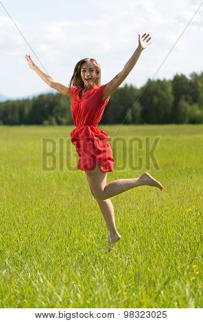 Young Girl In A Red Dress Jumping In A Field With Forest