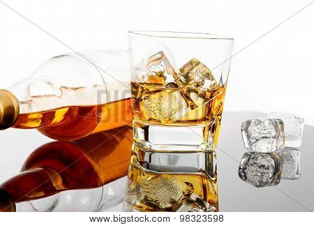 Glass Of Whiskey Near Bottle And Ice Cubes On Black Table With Reflection