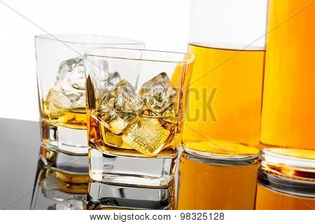 Two Glasses Of Whiskey Near Bottles On Black Background With Reflection