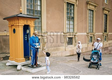 Tourists visit and photograph the guard of honor at the Royal pa