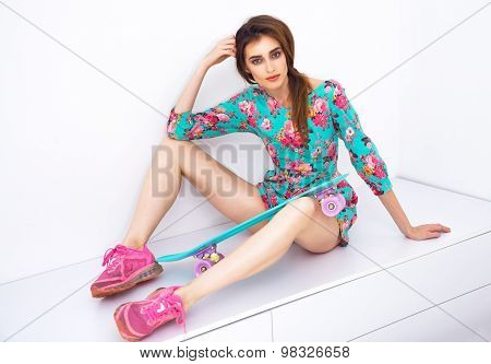 Fashion hipster girl in colorful dress with skateboard having fun . flirting against the white wall.