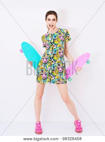 fashion sexy vogue model in colorful dress with bright ornament promote longboards in studio.