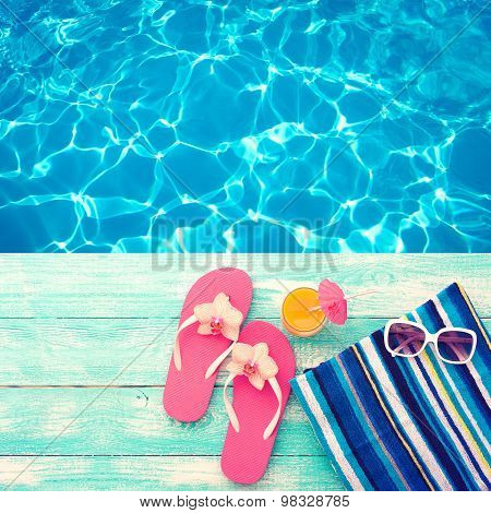 Summer vacation. Pink sandals by swimming pool.