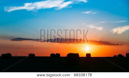 Summer Autumn Field Meadow With Hay Bales Silhouettes Under Suns