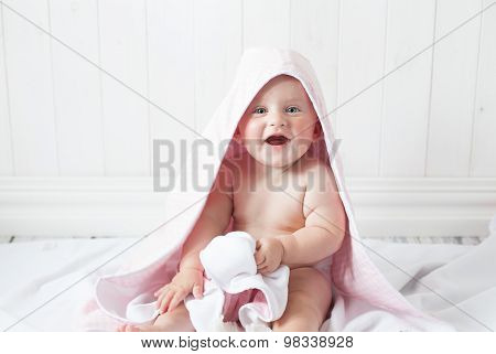 happy baby with a towel after the shower in bed at ho