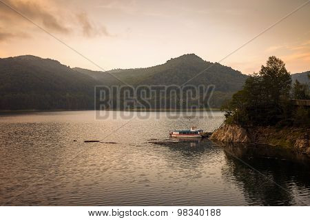 Small Boat On The Artificial Lake Behind The Bicaz Dam, At Sunset
