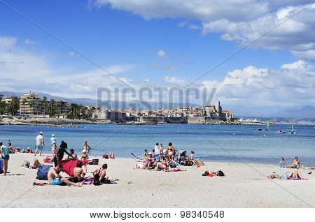 ANTIBES, FRANCE - MAY 15: People sunbathing on the beach on May 15, 2015 in Antibes, France. The fort Chateau Grimaldi, in the background, is the seat of the Picasso Museum
