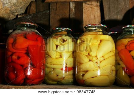 Home preserved peppers in glass jars in cellar, closeup