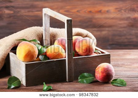 Fresh peaches in crate with sackcloth on wooden background