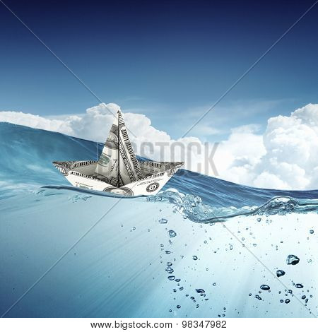Ship made of dollar banknote floating in water