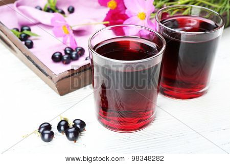 Glasses of fresh blackcurrant juice on wooden table near tray with flowers, closeup