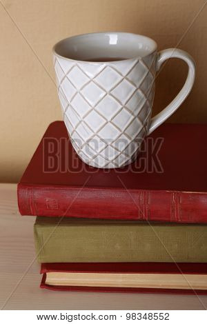 Cup of tea with stack of books on wooden table on light wall background