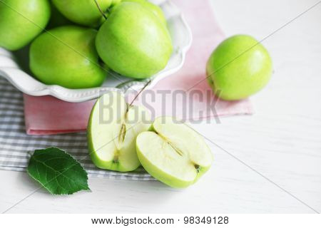 Green apples in bowl on table with napkins, closeup