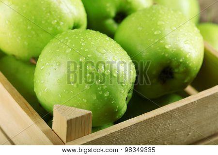 Ripe green apple in crate close up
